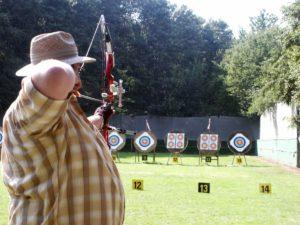 Ein Schütze mit Compoundbogen zielt auf Scheiben.